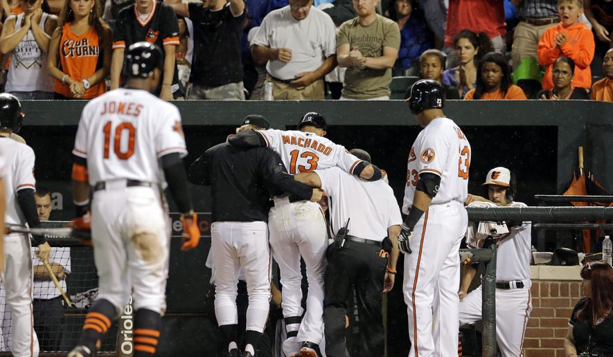 Baltimore Orioles' Manny Machado (13) is assisted into the clubhouse by manager Buck Showalter, left, and head athletic trainer Richie Bancells after grounding out in the third inning of a baseball game against the New York Yankees, Monday, Aug. 11, 2014, in Baltimore. (AP Photo/Patrick Semansky)