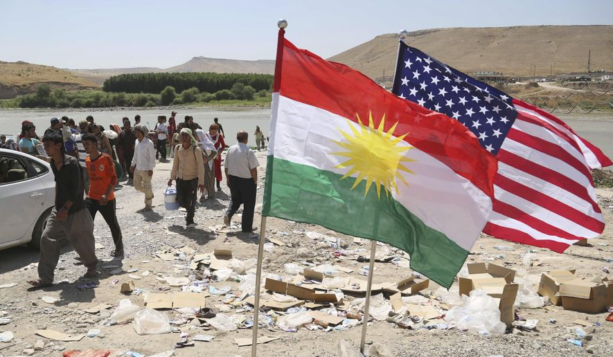 U.S. and Kurdish flags flutter in the wind while displaced Iraqis from the Yazidi community cross the Syria-Iraq border at Feeshkhabour bridge over the Tigris River at Feeshkhabour border point, in northern Iraq, Sunday, Aug. 10, 2014. Kurdish authorities at the border believe some 45,000 Yazidis passed the river crossing in the past week and  thousands more are still stranded in the mountains. (AP Photo/ Khalid Mohammed)