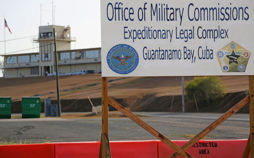 FILE - This June 17, 2013, file photo, shows a sign outside the Courthouse One Expeditionary Legal Complex at Naval Station Guantanamo Bay, Cuba. U.S. prosecutors are asking a military judge to reconsider his decision to try one of the men accused of plotting the Sept. 11 attack apart from the other four. Prosecutors have asked Army Col. James Pohl to hear arguments on their emergency motion involving Binalshibh first thing Monday, Aug. 11, 2014, at a pretrial hearing at the Guantanamo Bay naval base in Cuba. (AP Photo/Bill Gorman, File)