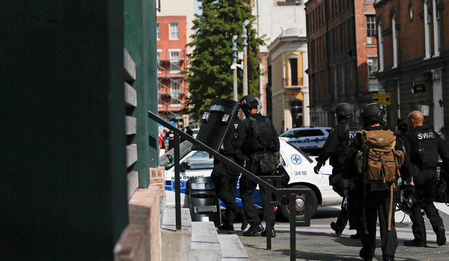 A SWAT team leaves the Westin Hotel on Sunday, Aug. 10, 2014. New Orleans police say one man is dead and another critically wounded after a shooting. (AP Photo/ NOLA.com / The Times-Picayune, Julia Kumari Drapkin)