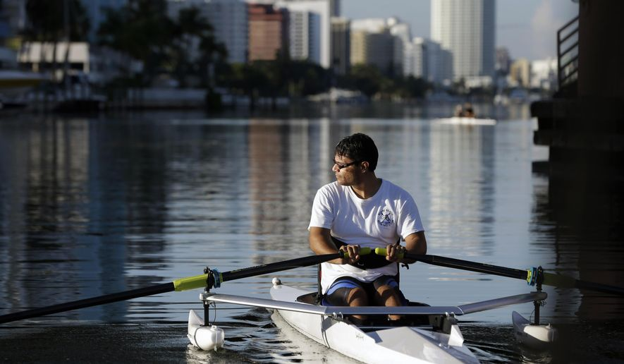 In this Aug. 6, 2014 photo, Juan Carlos Gil, of Miami, rows on the Indian Creek waterway during a training session in Miami Beach, Fla. Gil, who has cerebral palsy and is legally blind, participates in the adaptive rowing program for people with disabilities at the Miami Beach Rowing Club. The free program runs on private donations with a small coaching staff and a group of volunteers. It is open to people with all disabilities. (AP Photo/Lynne Sladky)