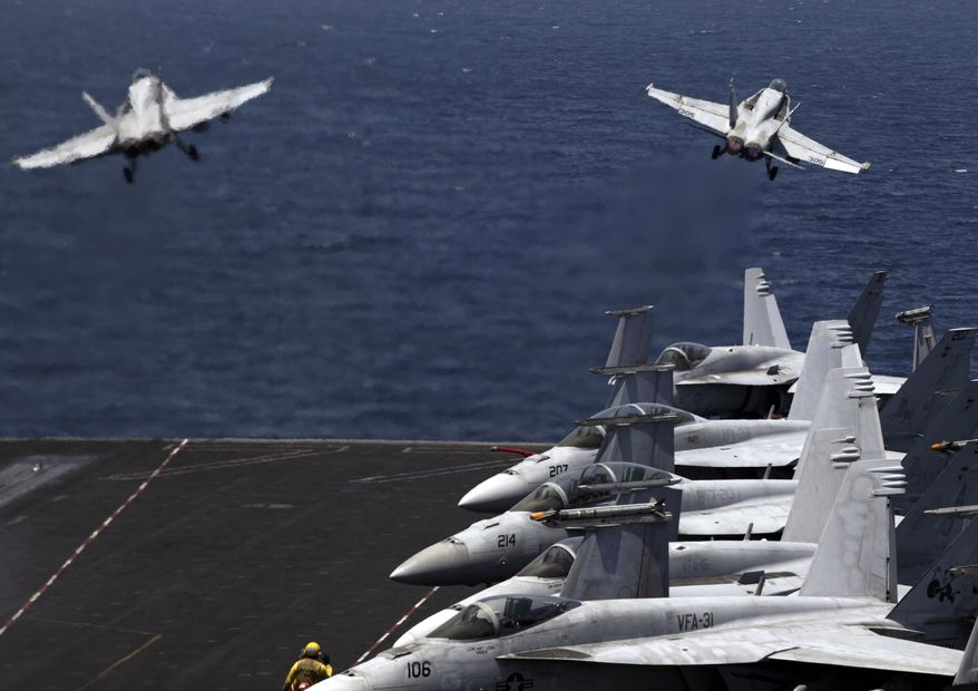 U.S. F/A-18 fighter jets take off for mission in Iraq from the flight deck of the U.S. Navy aircraft carrier USS George H.W. Bush, in the Persian Gulf, Monday, Aug. 11, 2014. U.S. military officials said American fighter aircraft struck and destroyed several vehicles Sunday that were part of an Islamic State group convoy moving to attack Kurdish forces defending the northeastern Iraqi city of Irbil. (AP Photo/Hasan Jamali)