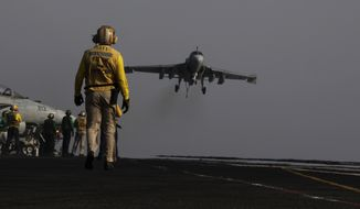 THIS CORRECTs THE TYPE OF WARPLANE IS AN EA-6B -- An  EA-6B coming from Iraq lands on the flight deck of the U.S. Navy aircraft carrier USS George H.W. Bush on Sunday, Aug. 10, 2014 in the Persian Gulf. Aircrafts aboard the George H.W. Bush are flying missions over Iraq after U.S. President Barack Obama authorized airstrikes against Islamic militants and food drops for Iraqis trapped by the fighters. (AP Photo/Hasan Jamali)