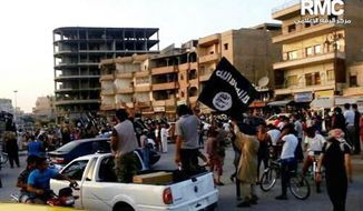FILE - This undated file photo posted by the Raqqa Media Center, a Syrian opposition group, on Monday, June 30, 2014, which has been verified and is consistent with other AP reporting, shows fighters from extremist Islamic State group during a parade in Raqqa, Syria. Activists have reported two cases of stoning this month in the Syrian northern province of Raqqa. The first case of stoning occurred in the town of Tabqa. A day after the July 17, 2014, stoning of Shamseh Mohammed Abdullah, 26, Faddah al-Sayed Ahmad was stoned to death in the provincial capital of Raqqa. (AP Photo/Raqqa Media Center, File)