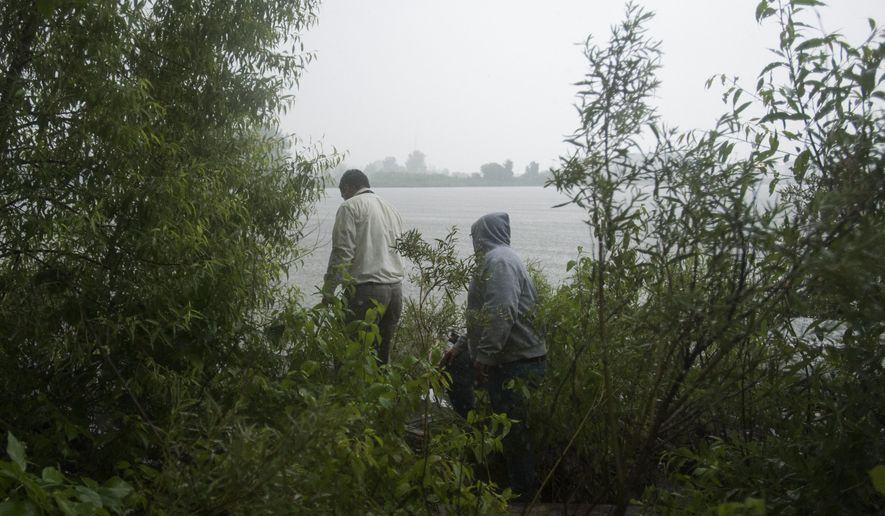 David Harran, Bay City public works director, and Gary Korthals walk out to see the leaking 36-inch storm drain in the Saginaw River Monday, Aug. 11, in Bay City. (AP Photo/The Bay City Times, Yfat Yossifor)