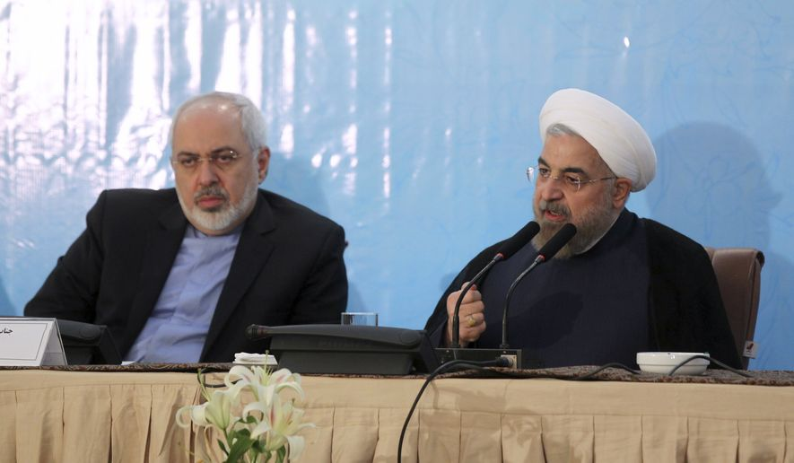 """In this photo released by the official website of the office of the Iranian Presidency, Iran's President Hassan Rouhani, right, speaks during an annual meeting of Iranian ambassadors as Foreign Minister Mohammad Javad Zarif listens, in Tehran, Iran, Monday, Aug. 11, 2014. Rouhani has offered his harshest criticism yet of hard-liners opposed to making a deal over its contested nuclear program with world powers, saying they should go """"to hell."""" (AP Photo/Mohammad Berno, Iranian Presidency Office)"""
