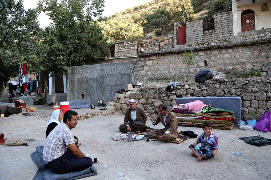 Displaced Iraqis from the Yazidi community settle near the holy Lalish temple in the Mountains of Shikhan near Dahuk, 260 miles (430 kilometers) northwest of Baghdad Monday, Aug. 11, 2014. President Barack Obama authorized the airstrikes to protect U.S. interests and personnel in the region, including at facilities in Irbil, as well as Yazidi refugees fleeing militants. (AP Photo/ Khalid Mohammed)