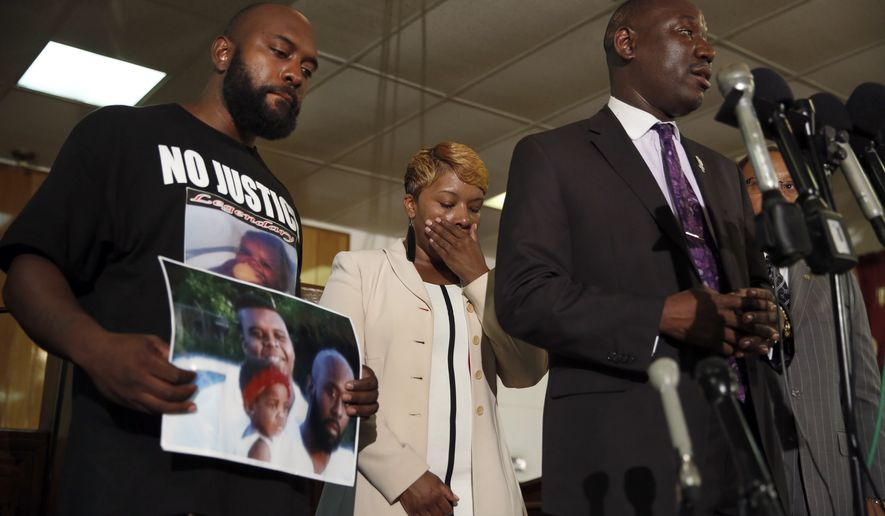 Lesley McSpadden, center, and Michael Brown Sr., left, the parents of Michael Brown, listen as attorney Benjamin Crump speaks during a news conference Monday, Aug. 11, 2014, in Jennings, Mo. Michael Brown, 18, was shot and killed in a confrontation with police in the St. Louis suburb of Ferguson, Mo, on Saturday, Aug. 9, 2014. (AP Photo/Jeff Roberson)