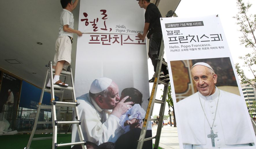 "Workers set up a poster of Pope Francis' photo exhibition ""Hello, Pope Francis!"" at the Sejong Culture Center in Seoul, South Korea. The pope is scheduled to make a five-day trip to South Korea, starting Wednesday. (AP Photo/Ahn Young-joon)"