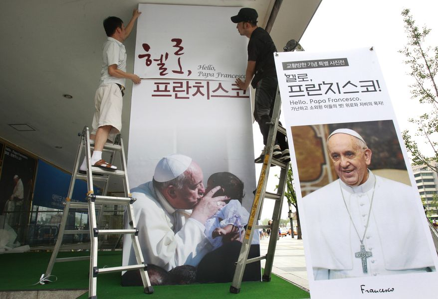 """Workers set up a poster of Pope Francis' photo exhibition """"Hello, Pope Francis!"""" at the Sejong Culture Center in Seoul, South Korea. The pope is scheduled to make a five-day trip to South Korea, starting Wednesday. (AP Photo/Ahn Young-joon)"""
