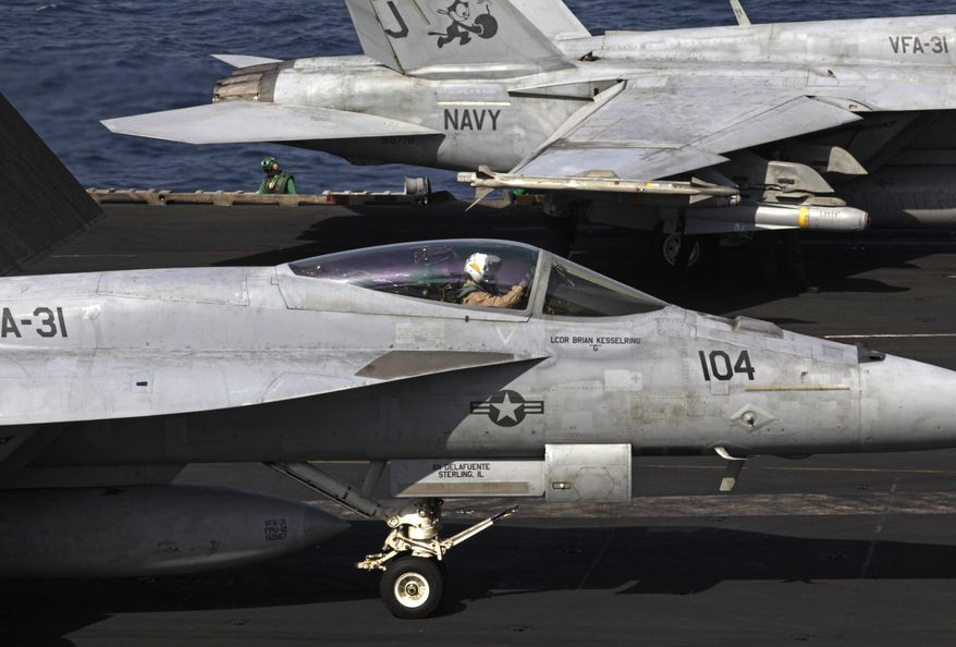 U.S. F/A-18 fighter jets prepare to take off for Iraq from the flight deck of the U.S. Navy aircraft carrier USS George H.W. Bush in the Persian Gulf.  (AP Photo/Hasan Jamali)