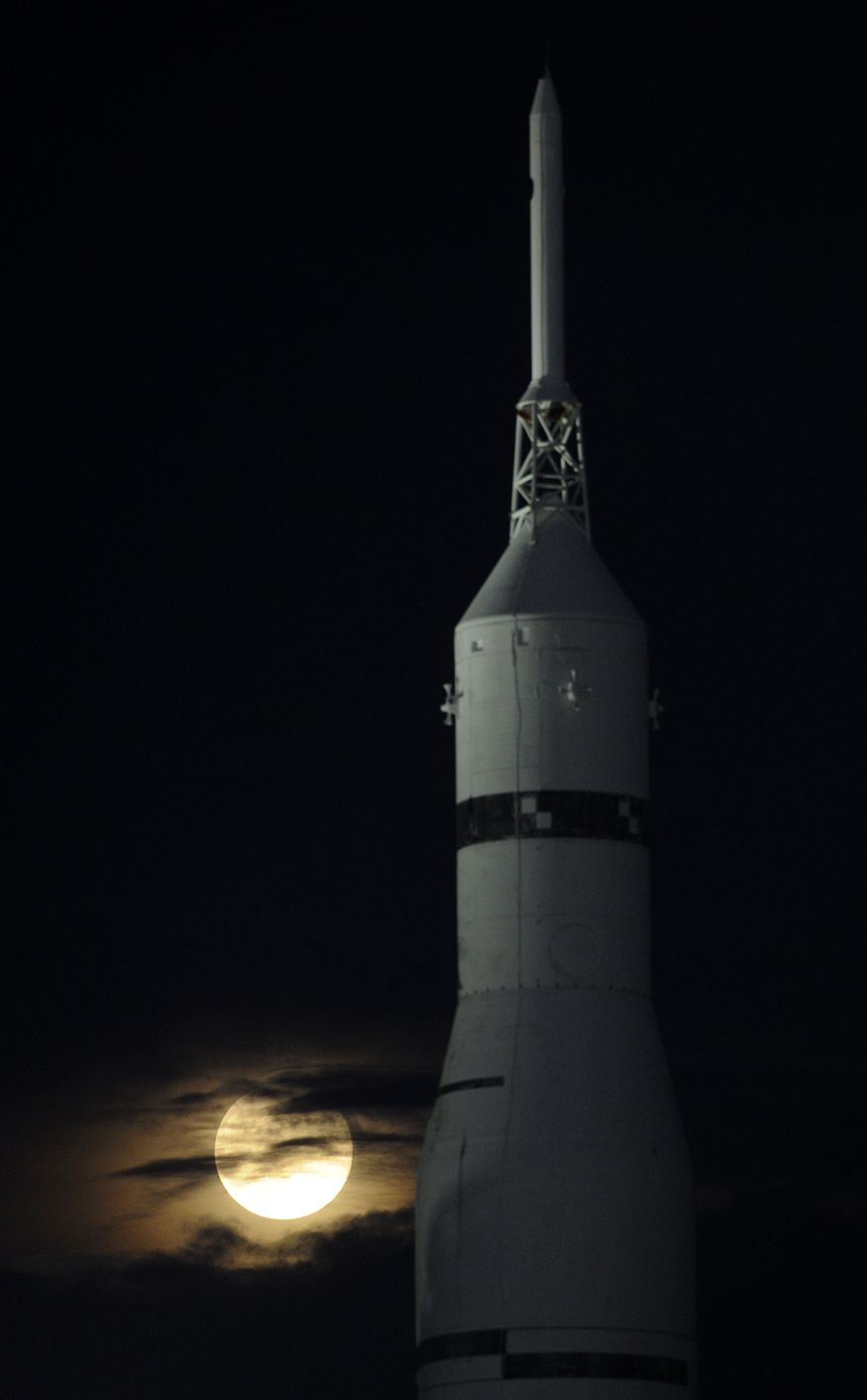"""The Moon rises next to a Saturn 1B rocket at the U.S. Space and Rocket Center Sunday, Aug. 10, 2014 in Huntsville, Ala.  The 224-foot-tall Saturn 1B was a forerunner of the Saturn V launch vehicle for NASA missions to the moon. The phenomenon, which scientists call a """"perigee moon,"""" occurs when the moon is near the horizon and appears larger and brighter than other full moons. (AP Photo/Eric Schultz, AL.com)"""