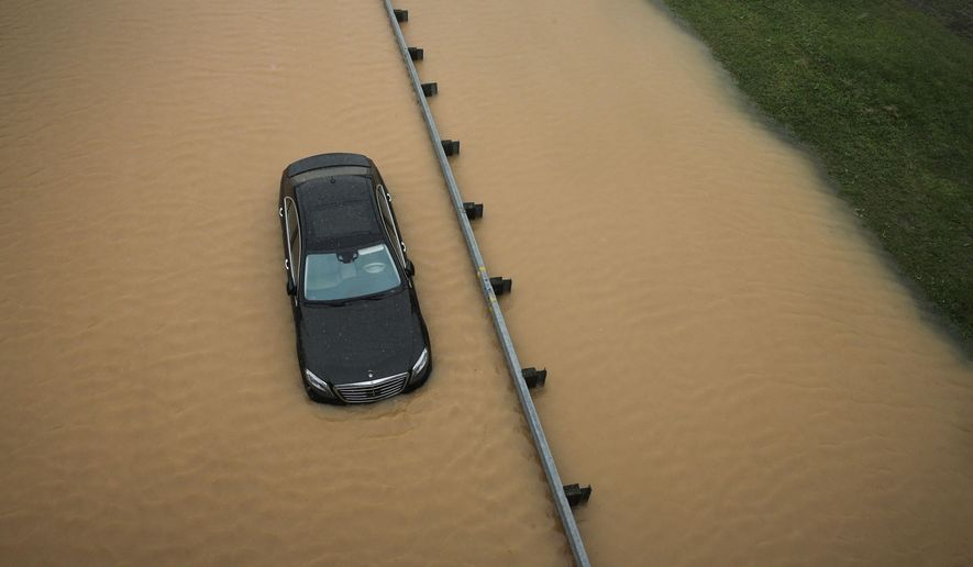 A partially submerged car sits on a flooded section of Interstate 695 in Baltimore, Tuesday, Aug. 12, 2014, after heavy rains fell across the Mid-Atlantic region. Officials shut down the Baltimore beltway in both directions at Quarantine Road due to heavy flooding. (AP Photo/Patrick Semansky)