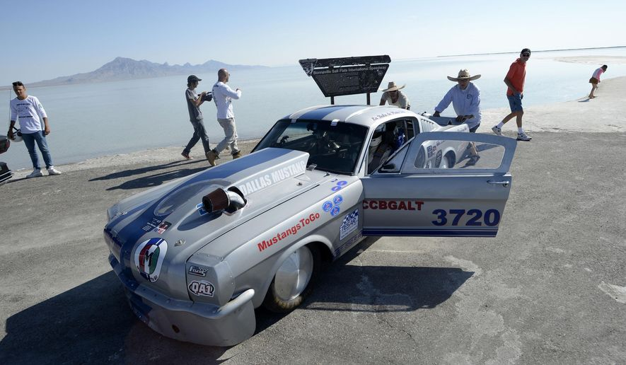 """In this photo taken on Monday, Aug. 11, 2014, Todd Landon, from Minneapolis, pushes his Mustang race car on to the access road where pavement ends and salt begins at the Bonneville Salt Flats, Utah. He parked it there to at least get some video and photos of the car.  Three or four inches of water covers the salt flats from rains last week putting an end to """"Speed Week."""" (AP Photo/The Salt Lake Tribune, Al Hartmann)  DESERET NEWS OUT; LOCAL TELEVISION OUT; MAGS OUT"""