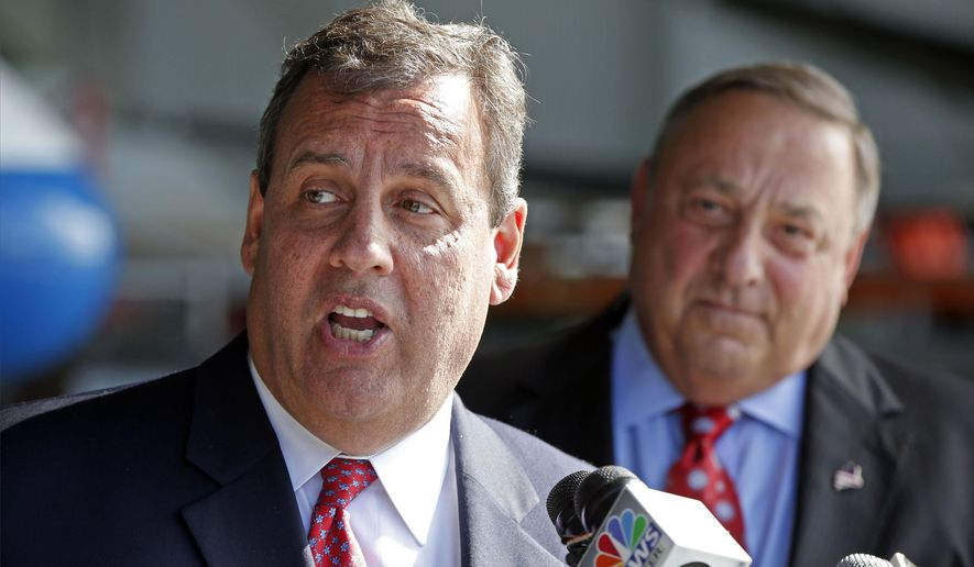New Jersey Gov. Chris Christie (left) speaks to reporters while visiting C&L Aviation with Maine Gov. Paul LePage on Aug. 12, 2014, in Bangor, Maine. Christie returned to Maine to campaign for LePage's re-election campaign. (Associated Press) **FILE**
