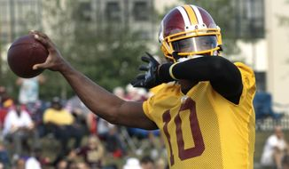 The Washington Redskins' quarterback Robert Griffin III,  throosw a pass in the Redskins' morning practice at the Bon Secours Washington Redskins Training Center Monday, Aug. 11, 2014, in Richmond, Va.  (AP Photo/Richmond Times-Dispatch, P. Kevin Morley )