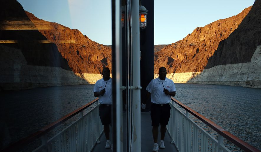 In this July 20, 2014 photo, the bathtub ring of light minerals that delineates the high water mark is seen reflected in a widow of the Desert Princess tour boat near Hoover Dam on Lake Mead at the Lake Mead National Recreation Area in Nevada. A 14-year drought has caused the water level in the reservoir to shrink to its lowest point since it was first filled in the 1930s. (AP Photo/John Locher)