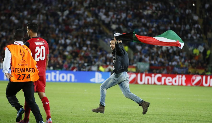 A fan runs onto the pitch holding a palestinian flag during the UEFA Super Cup soccer match between Real Madrid and Sevilla in Cardiff City Stadium, in Cardiff, Wales, Tuesday, Aug. 12, 2014. (AP Photo/Alastair Grant)