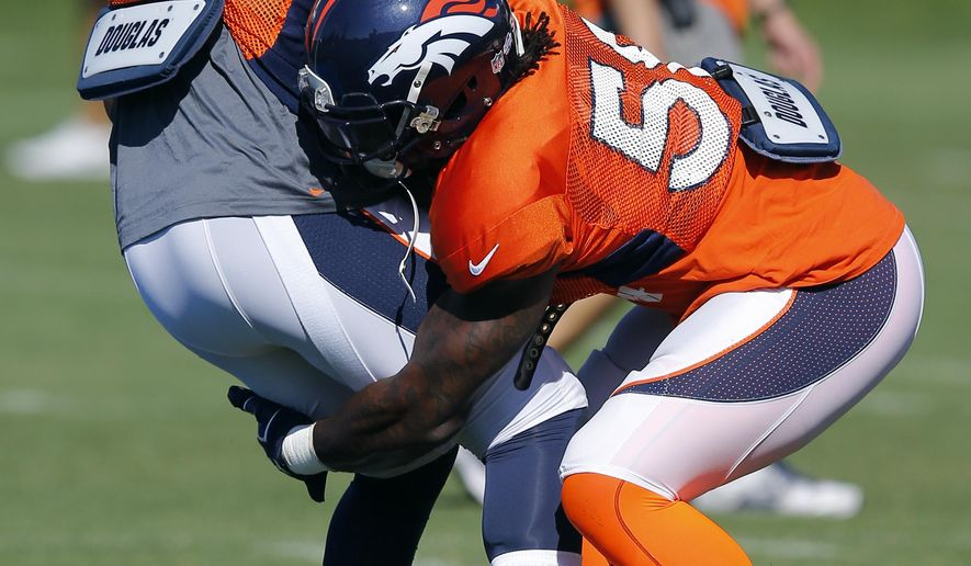 Denver Broncos' Danny Trevathan runs a drill against Lerentee McCray (55) during NFL football training camp on Tuesday, Aug 12, 2014, in Englewood, Colo.  Trevathan was injured later in practice. (AP Photo/Jack Dempsey)