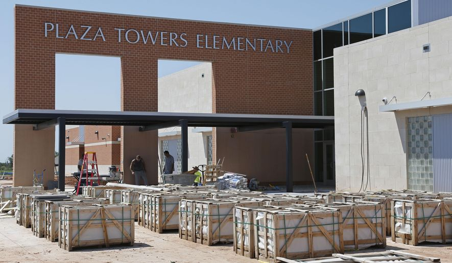 Construction continues on the exterior of the new Plaza Towers elementary school in Moore, Okla., Tuesday, Aug. 12, 2014. Plaza Towers Elementary School was destroyed by an EF5 tornado on May 20, 2013, killing seven students. A memorial at the entrance, dedicated to the seven students who were killed, is expected to be completed in the fall. (AP Photo/Sue Ogrocki)