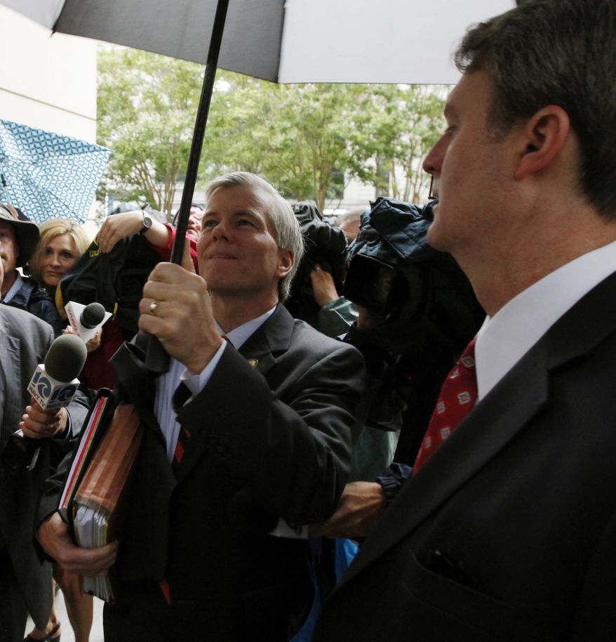 Former Virginia governor Bob McDonnell lowers his umbrella as he prepares to enter the federal courthouse in Richmond, Va., Tuesday, Aug. 12, 2014, where the third week of the federal corruption trial against himself and his wife Maureen continues. On the right is one of his attorneys, John L. Brownlee.  (AP Photo/Richmond Times-Dispatch, Bob Brown)