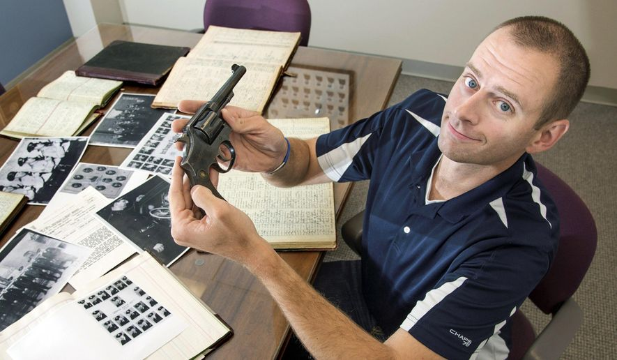 In this July 18, 2014 photo, Matt Rivers, a detective with Urbana, Ill., Police Department, shows off a .38 Special revolver once owned by the department's police chief in 1933. The police chief left after one year. A six-year member of the department, Rivers is spearheading an effort to put together a picture book and a video of the department's history by this time next year, which will be the 160th anniversary of the city's first marshal. (AP Photo/The News-Gazette, Heather Coit) MANDATORY CREDIT