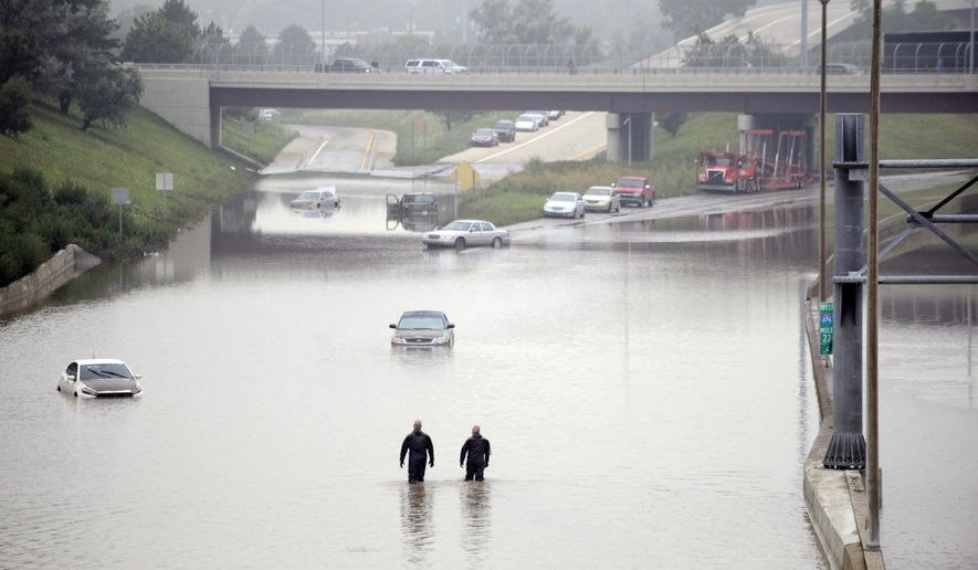 Cars are stranded along a flooded stretch of Interstate 696 at the Warren, Mich., city limits Tuesday morning, Aug. 12, 2014. Police divers are searching for anyone trapped in their vehicles. Warren Mayor James Fouts said roughly 1,000 vehicles had been abandoned in floodwaters in the suburb where many roads were closed after 5.2 inches of rain fell Monday. (AP Photo/Detroit News, David Coates)  DETROIT FREE PRESS OUT; HUFFINGTON POST OUT