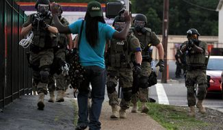 Police wearing riot gear walk toward a man with his hands raised Monday, Aug. 11, 2014, in Ferguson, Mo. Authorities have made several arrests in Ferguson, where crowds have looted and burned stores, vandalized vehicles and taunted police after a vigil for an unarmed black man who was killed by police. (AP Photo/Jeff Roberson) ** FILE **