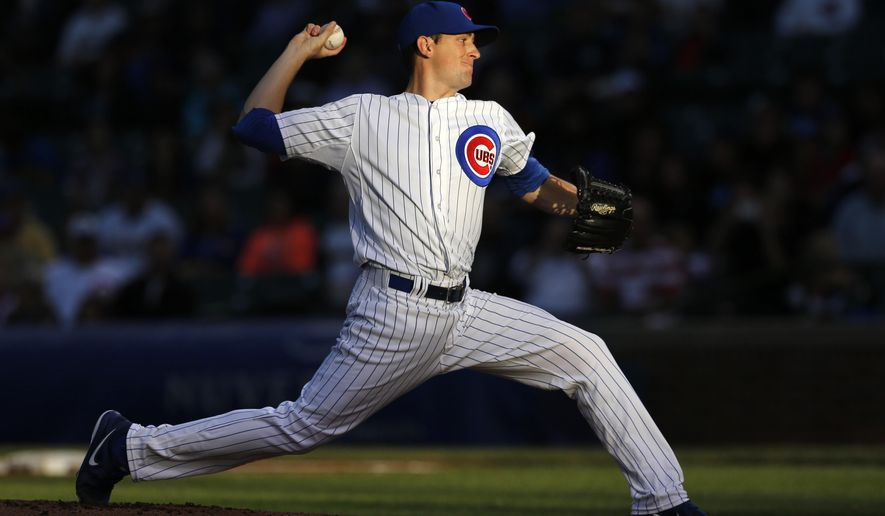 Chicago Cubs starting pitcher Kyle Hendricks delivers in a setting sun during the first inning of a baseball game against the Milwaukee Brewers Tuesday, Aug. 12, 2014, in Chicago. (AP Photo/Charles Rex Arbogast)