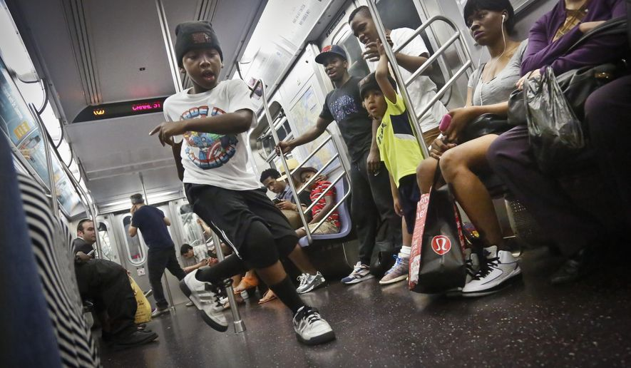 FILE - In this June 17, 2014 file photo,  Marc Mack, 8, a member with the dance troupe W.A.F.F.L.E., which stands for We Are Family For Life Entertainment, performs on a subway, in New York. Subway acrobats, dancers and musicians on Tuesday, Aug 12, 2014 decried what they said was heavy-handed policing, gathering outside City Hall to join critics of a police clampdown on minor offenses. Transit rules generally allow performing for tips in parts of subway stations, but not in trains or with amplifiers, unless artists have permits. More than 240 subway performers have been arrested so far this year, about four times as many as during the same period last year, according to police statistics. (AP Photo/Bebeto Matthews, File)