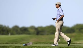 President Barack Obama prepares to tee off while golfing at Vineyard Golf Club, Tuesday, Aug. 12, 2014, in Edgartown, Mass., on the island of Martha's Vineyard. President Obama is taking a two-week summer vacation on the island. (AP Photo/Steven Senne)