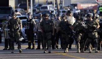 Police in tactical gear stand in a street Tuesday, Aug. 12, 2014, in Ferguson, Mo. Racial tensions have run high in in the predominantly black city of Ferguson, following the shooting death by police of Michael Brown, 18, an unarmed black man. (AP Photo/Jeff Roberson)