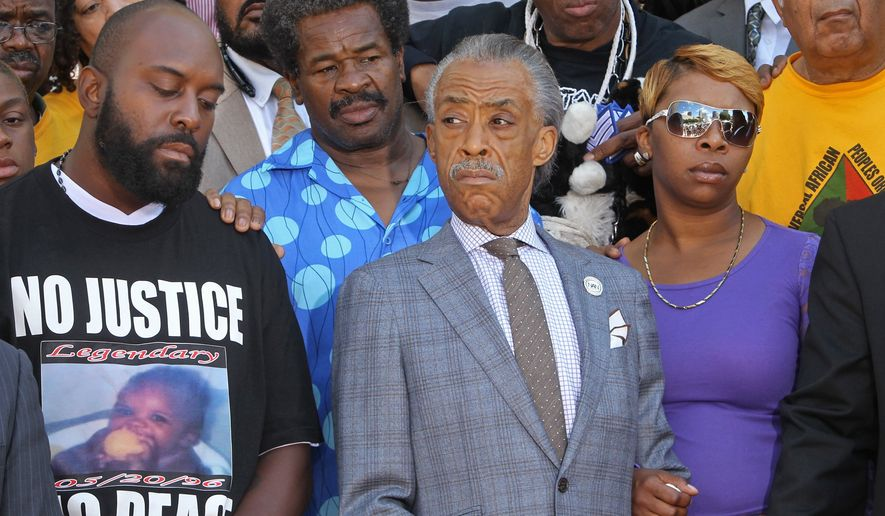 Michael Brown Jr.'s parents, Michael Brown Sr., left, and Lesley McSpadden, right, stand next to the Rev. Al Sharpton on Tuesday, Aug. 12, 2014, in St. Louis. Sharpton pressed police Tuesday to release the name of the officer who fatally shot Brown Jr., an unarmed teenager in suburban St. Louis, but he also pleaded for calm after two nights of violent protests. (AP Photo/St. Louis Post-Dispatch, J.B. Forbes)