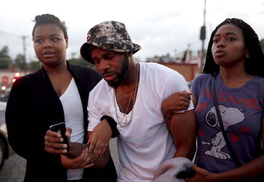 A man is helped by two women following an encounter with police Monday, Aug. 11, 2014, in Ferguson, Mo. The FBI opened an investigation Monday into the death of 18-year-old Michael Brown, who police said was shot multiple times Saturday after being confronted by an officer in Ferguson. Authorities in Ferguson used tear gas and rubber bullets to try to disperse a large crowd Monday night that had gathered at the site of a burned-out convenience store damaged a night earlier, when many businesses in the area were looted. (AP Photo/Jeff Roberson)