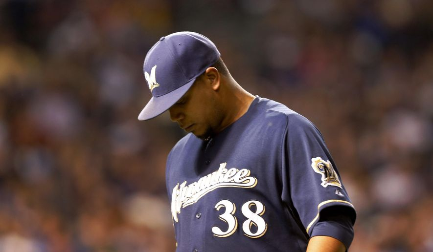Milwaukee Brewers starting pitcher Wily Peralta leaves the game during the seventh inning of a baseball game against the Chicago Cubs Tuesday, Aug. 12, 2014, in Chicago. (AP Photo/Charles Rex Arbogast)