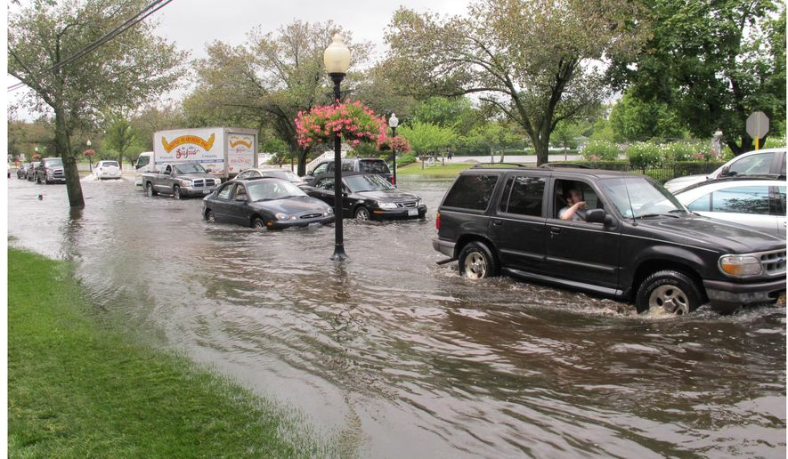 Vehicles attempt to maneuver down a flooded Montauk Highway in Babylon,  N.Y., Wednesday Aug. 13, 2014. The National Weather Service says parts of Long Island experienced record-setting rainfall in the past 24 hours. In one community, more than 13 inches of rain was reported. (AP Photo/Frank Eltman)