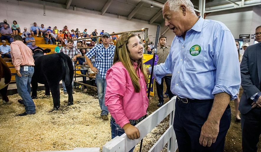 Illinois Gov. Pat Quinn congratulates Shaelye Varner, center, on her Grand Champion Steer during the Governor's Sale of Champions at the Illinois State Fair, Tuesday, Aug. 12, 2014, in Springfield, Ill. A record $100,000-plus was bid for Varner's steer, which is named Ted because she thinks he is like a teddy bear. (AP Photo/The State Journal-Register, Justin L. Fowler)