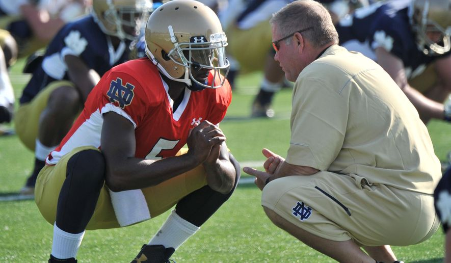 FILE - In this Aug. 9, 2014, file photo, Notre Dame coach Brian Kelly, right, talks with quarterback Everett Golson during practice in South Bend, Ind. Golson has reclaimed the job as Notre Dame's starting quarterback after being suspended last semester for academic impropriety. Coach Brian Kelly on Wednesday, Aug. 13, 2014, said Golson would start against Rice on Aug. 30 and said he hopes he will be the starter for the entire season.  (AP Photo/Joe Raymond, FILE)