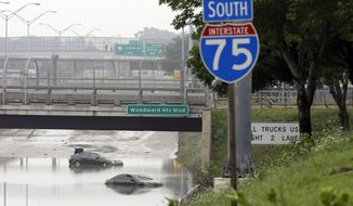 Cars are stranded along a flooded stretch of Interstate 75 in Hazel Park, Mich., Tuesday, Aug. 12, 2014. Fearing more motorists could become stranded a day after a storm dumped more than 6 inches of rain in some places in and around Detroit, the state warned commuters against driving in affected areas Tuesday morning. (AP Photo/Carlos Osorio)