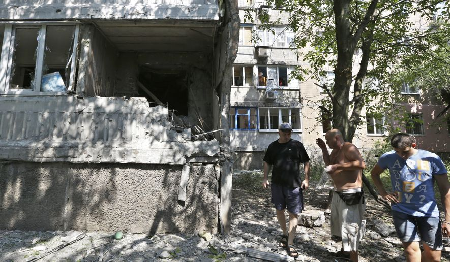 Local residents react as they inspect the damage after shelling in Donetsk, eastern Ukraine, Wednesday, Aug. 13, 2014. At least three people have been killed in the separatist-controlled city of Donetsk in eastern Ukraine as the government intensifies its shelling campaign. (AP Photo/Sergei Grits)
