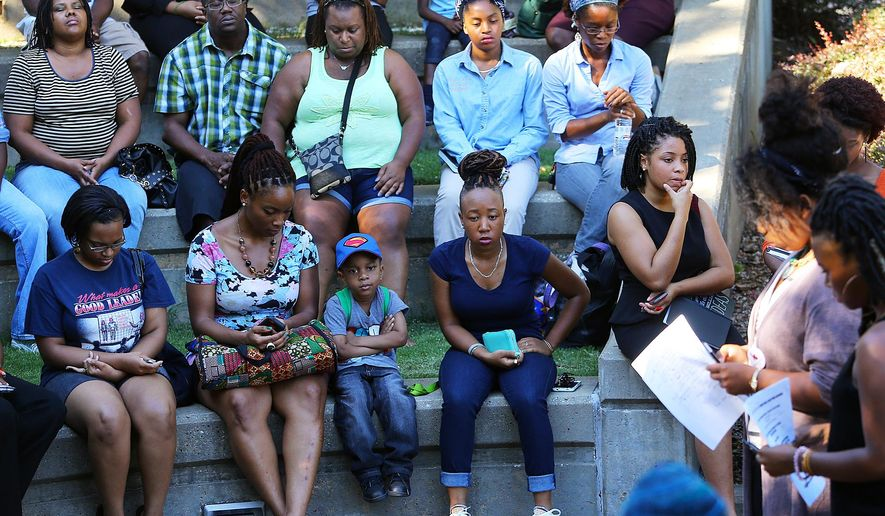 Dozens observe a moment of silence to open a town hall meeting in response to the police shooting of Michael Brown in a St. Louis suburb, at the Martin Luther King Jr. National Historic Site on Wednesday, Aug. 13, 2014, in Atlanta. (AP Photo/Atlanta Journal Constitution, Curtis Compton)