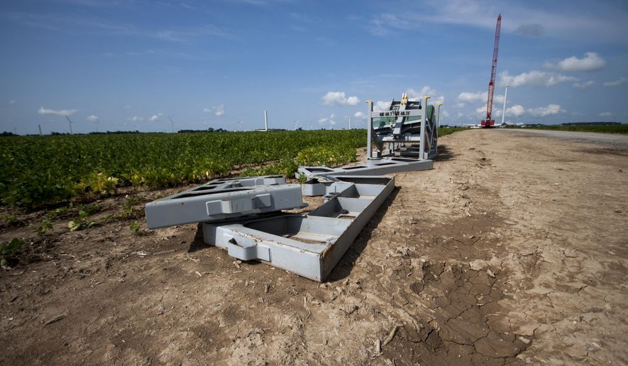 In this photo taken on Aug. 7, 2014, parts sit on the ground as a crane used to construct wind turbine moves into position to begin construction in Akron Township, Mich. Crews are making progress on construction of a wind power project in Michigan that will expand Consumers Energy's renewable energy options. (AP Photo/The Saginaw News, Coty Giannelli) ALL LOCAL TELEVISION OUT; LOCAL TELEVISION INTERNET OUT MBO  (REV-SHARE)