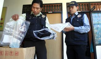 Indonesian forensic police officers view evidence related to the death of an American woman at a police station in Bali, Indonesia, Wednesday, Aug. 13, 2014. The body of Sheila von Wiese Mack, 62, was found Tuesday stuffed inside a suitcase inside the trunk of a taxi parked in front of an upscale hotel in Bali's Nusa Dua area. Police have arrested her daughter and her daughter's boyfriend in relation to the death. (AP Photo/Firdia Lisnawati) ** FILE **