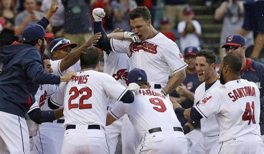 Cleveland Indians' Zack Walters, top, is mobbed by teammates after Walters hit a game-winning solo home run off Arizona Diamondbacks relief pitcher Randall Delgado in the ninth inning of the first baseball game of a doubleheader, Wednesday, Aug. 13, 2014, in Cleveland. The Indians defeated the Diamondbacks 3-2. (AP Photo/Tony Dejak)