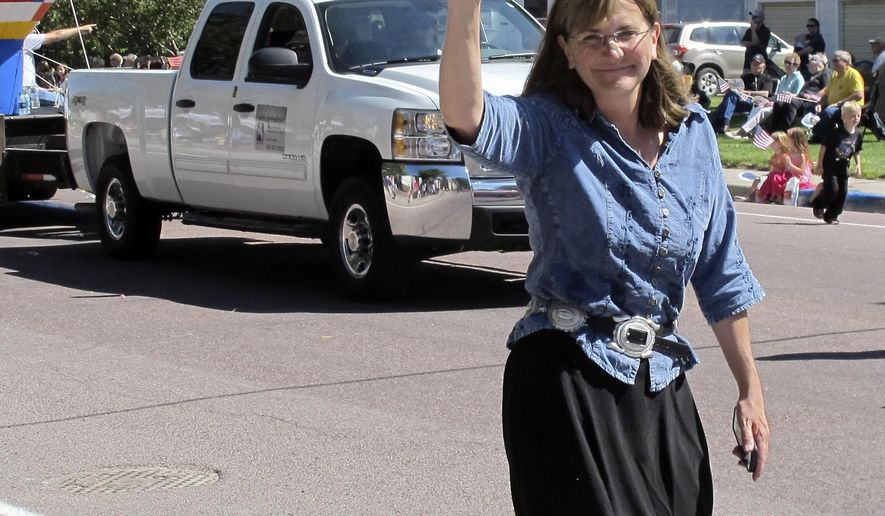 In this photo taken on July 31, 2014, Cindy Hill waves to the crowd during a parade in Torrington, Wyo. Hilll, the Wyoming Superintendent of Public Instruction, is seeking the Republican Party nomination for governor in the Aug. 19 primary election. (AP Photo/Ben Neary)