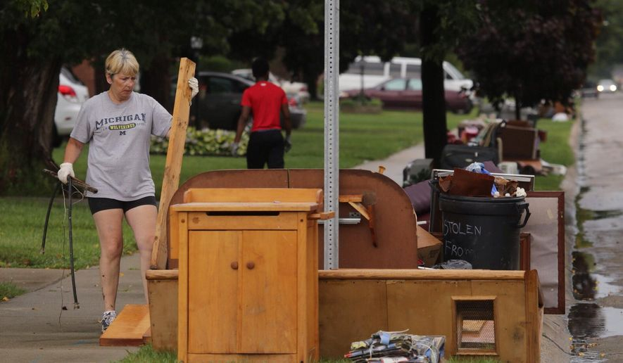 Terri Quick, of Center Line, Mich., carries items to the trash from her house that were in a floodwaters, on Tuesday, Aug. 12, 2014, after heavy rains flooded many areas in metro Detroit on Monday. (AP Photo/Detroit Free Press, Ryan Garza)