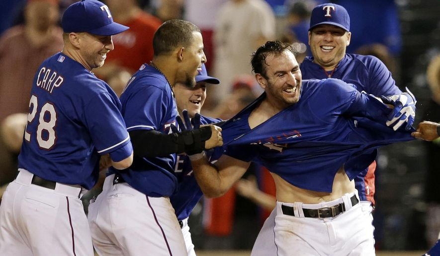 Texas Rangers' Mike Carp (28), from left, Rougned Odor, Daniel Robertson and Shawn Tolleson, right, celebrate with Adam Rosales, second from right, after Rosales earned a walk against Tampa Bay Rays relief pitcher Cesar Ramos in the 14th inning of a baseball game, Tuesday, Aug. 12, 2014, in Arlington, Texas. The Rangers' Nick Martinez scored on Rosales' walk in the 3-2 Rangers win.  (AP Photo/Tony Gutierrez)