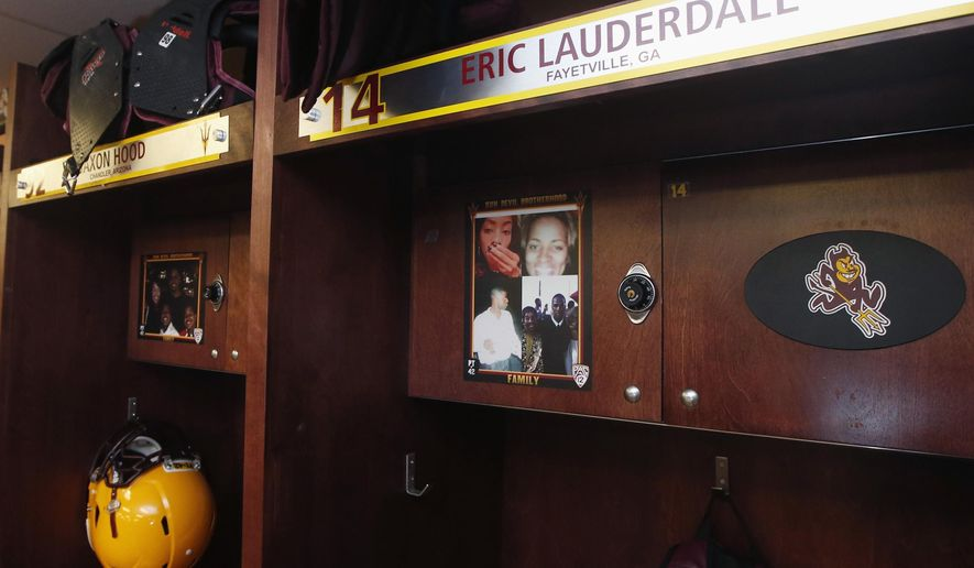 Arizona State's Eric Lauderdale has a photo of his late parents along with his grandmother and sister attached to his locker in the Arizona State football team locker room Monday, Aug. 11, 2014, in Tempe, Ariz.  Each player and coach on Arizona State's team has a photo above their locker of someone who has inspired them. There are mothers, fathers, siblings, grandparents, a few coaches. Coach Todd Graham had them all do it so they can remember it's not just their teammates they're playing for. (AP Photo/Ross D. Franklin)
