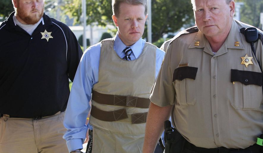 FILE - In this April 12, 2011 file photo, murder suspect Christopher Coleman, center, is escorted to the Perry County Courthouse in Pinckneyville, Ill., during his trial. On Tuesday, Aug. 12, 2014, an Illinois appeals court reinstated the wrongful-death lawsuit claiming Joyce Meyer Ministries should have done more to prevent Coleman from killing his family. Coleman strangled his wife and two sons inside the family's Columbia home in 2009. It was filed on behalf of the family of Sheri Coleman, Christopher Coleman's wife. (AP Photo/The Belleville News-Democrat, Derik Holtmann, File)