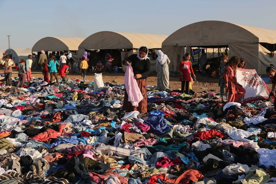 Displaced Iraqis from the Yazidi community look for clothes to wear among items provided by a charity organization at the Nowruz camp, in Derike, Syria. (Associated Press)